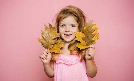 Smiling little girl playing with leaves and looking at camera. Autumn celebrate kids Clothing. Cute little child girl are getting ready for autumn sale. Close-up portrait.