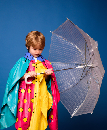 Autumn mood and the weather are warm and sunny and rain is possible. Cute little boy with colorfull umbrella. Rain and umbrella concept. Kids in rain. Stok Fotoğraf