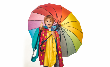 Smiling little boy playing with colorfull umbrella and looking at camera. Isolated object on white background. Rain and umbrella september concept. Stok Fotoğraf