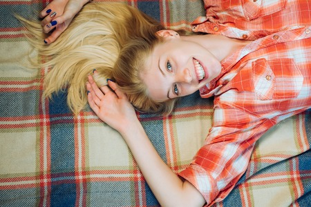 Blonde girl lies on a warm blanket. Smiling girl looking at camera. Autumn happy people and joy. Hello September. Model face.