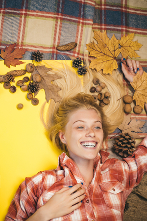 Blonde girl lies on a warm blanket. Smiling girl looking at camera. Autumn happy people and joy. Black friday shopping. Autumn design.