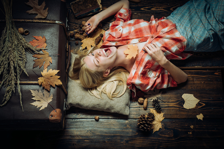 Blonde girl lies on a warm blanket. Beautiful sexy young woman lies on wood background. Autumn happy people and joy. Black friday shopping. Autumn design.
