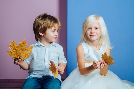 Cute little boy and girl holding leaf on color background. Children advertise your product and services. Autumn discounts on baby clothes. Stok Fotoğraf
