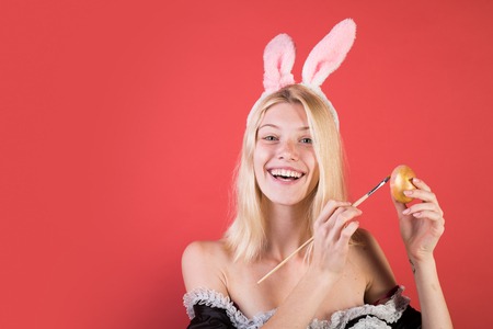 Happy young woman painting eggs on a red background. Cute bunny. Attractive young woman wearing bunny ears. Happy easter. Stock Photo