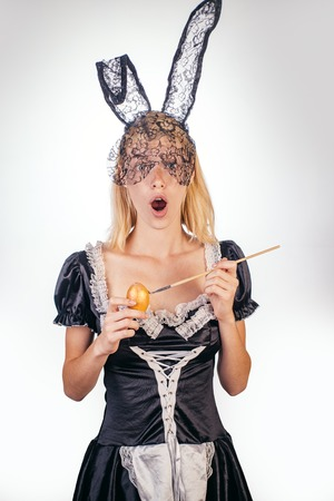 Happy young woman painting eggs on a white background. Attractive young woman wearing bunny ears. Happy easter. Funny bunny rabbit. Expression face.