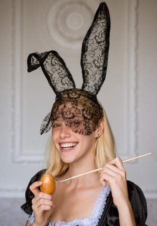 Happy young woman painting eggs. Beautiful sensual blonde. Close-up portrait. Blonde Girl wearing bunny ears and having Easter Eggs. Funny bunny rabbit. Stock Photo