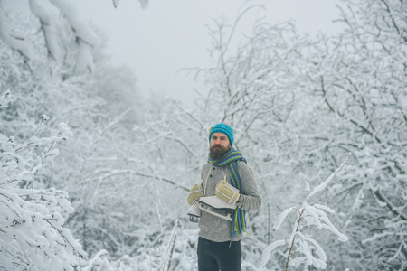 Winter sport and rest, Christmas. Temperature, freezing, cold snap, snowfall. Bearded man with skates in snowy forest. skincare and beard care in winter. Man in thermal jacket, beard warm in winter.