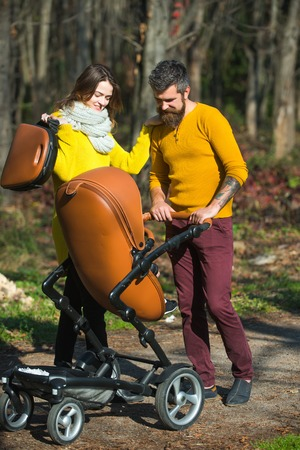 Family love concept. Happy parents walk in autumn park outdoor. Father and mother with baby stroller, family love. Carefree time together. Stock Photo