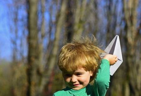 Child play with paper plane toy outdoor. Little child dream of flight. On the waves of my imagination. 版權商用圖片