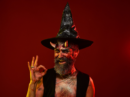 Halloween man with devil horns in witch hat show ok. Satan hipster smile with beard, blood, wounds on red background. Hell, death, evil, horror concept. Might, magic, witchcraft