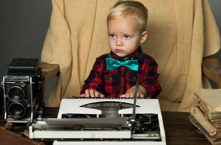 Baby boy type on retro typewriter at desk. It makes me feel so retro.