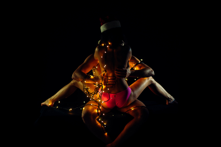 Christmas couple in love of man and woman in illuminated garland and santa claus hat kiss on black background, new year and games, love