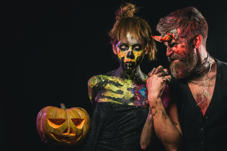 Halloween cosplay, holiday celebration. Couple in love on black background. Girl with skull makeup face and hipster devil. Woman skeleton and man with horns hold pumpkin. Trick or treat concept. Stock Photo