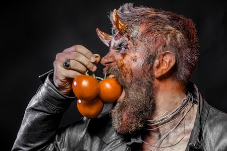 Halloween hipster devil hold red vitamin fruit. Man with satan horns bite tomatoes on black background. Autumn season concept. Harvest festival, holidays celebration. Food, vegetarian, diet.