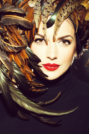 young sexy woman or girl with red lips on pretty face in beautiful feather hat brown color as halloween or carnival holiday costume, closeup 写真素材