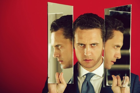 Agile business. Businessman, man or manager with serious face and stylish hair, haircut holding two mirrors in hands. Male profiles reflecting on pink background. Male beauty, copy space