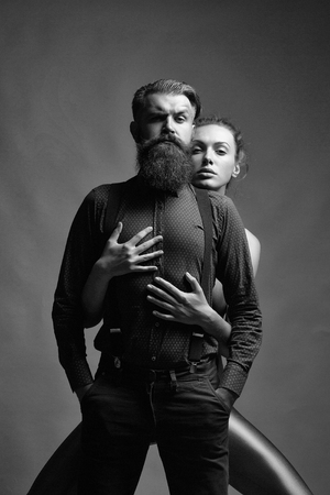 Pretty girl embraces handsome man hipster with beard and moustache fashion couple on grey background