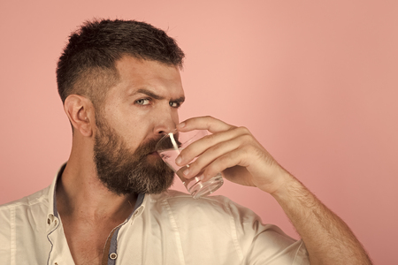man with beard on face drink water from glass
