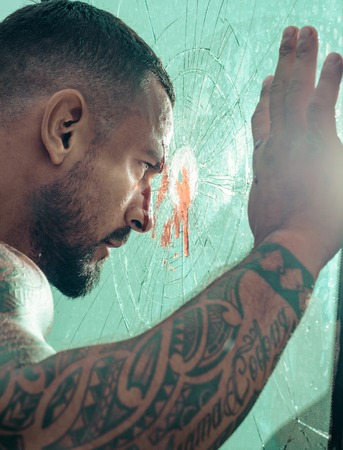 Man latin with muscular body looks through a broken window. Brutal handsome man with tattooed body. Portrait of brutal handsome latin male model. Stock Photo