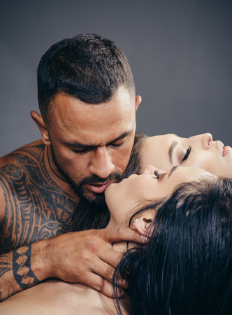 Passionate lover caressing arousing beautiful woman. Dominantning in the foreplay sexual game. Passionate woman with muscular latin lover. Dominant man. Night party - young lovers. Safety sex concept. Stock Photo