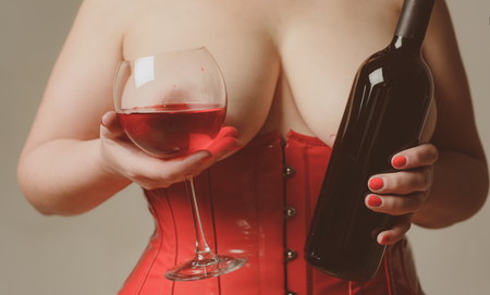 Sexy Plus Size Lingerie. Be Sexy. Woman in red holding wine glass. XXL big size. Female breast. Beautiful girl shows her gorgeous Breasts. Stock Photo
