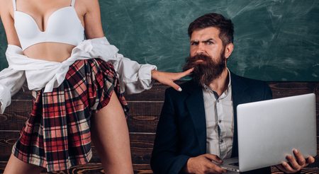 Educación sexual. Primer amor. Lencería sexy para mujer. Sexo loco. Mujer dominante. Lección de anatomía y educación en la escuela secundaria. Hablemos de sexo. El profesor de sexología barbudo mira a las alumnas. Foto de archivo