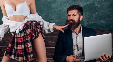 Seksuele voorlichting. Eerste liefde. Sexy lingerie voor vrouwen. Gekke seks. Dominante vrouw. Anatomische les en onderwijs op de middelbare school. Laten we praten over seks. Bebaarde leraar seksuologie kijkt naar vrouwelijke studenten. Stockfoto