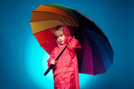 Child advertise your product and services. Handsome little guy in preparing for Autumn. Cute little child wearing in autumn clothes on autumn rain day. Cheerful boy in raincoat with colorful umbrella.