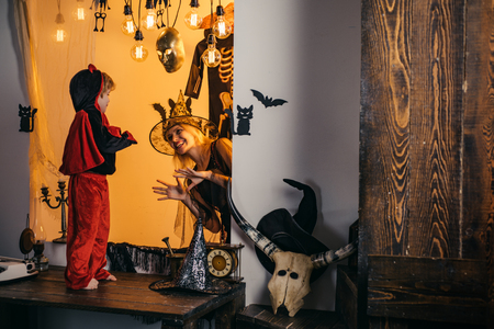 Happy family is preparing for a costume party. Cute happy little devil and his young mother wizard. 31 october. Magic hat. Best ideas for Halloween. Family halloween concept. Stok Fotoğraf