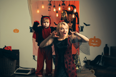 Mother wearing as witch, son wearing as devil. Boy in devil costume. Beautiful young woman with a child with pumpkins. Smiling mother and son. Mother and her child boy playing together.