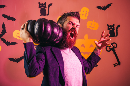 Happy hipster with bloody beard with pumpkins. Wizard, sorcerer, warlock. Scary face man with horror Make up holding Pumpkin head jack lantern on sky background.