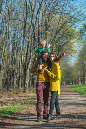 Family have fun in spring park. Loving father carry little son with wife while having fun outdoor. Beautiful one day, perfect the next