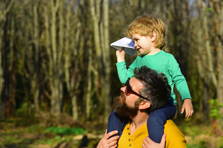 Flying is the perfect vocation for a man who wants to feel like a boy. Little son dream of flying on fathers shoulder. Child boy and father launch paper plane in park Фото со стока