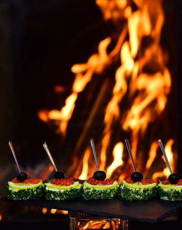 Snack food with red caviar and lemon on burning fire background. Caviar canape on snack counter. Flavor explosion