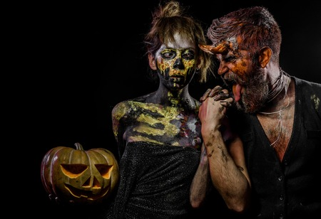 Halloween woman skeleton and man with horns hold pumpkin