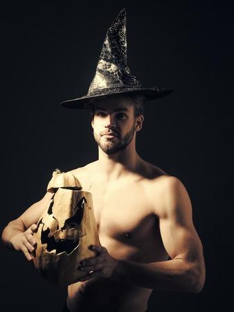 Halloween macho with muscular torso, biceps, triceps holding pumpkin