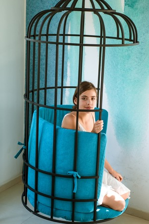 mental mind. prisoner woman in cage - home confinement. freedom of cute girl in cage chair. fashion slave in captivity of beauty. modern furniture design and home comfort. pretty woman in iron cage Stock Photo