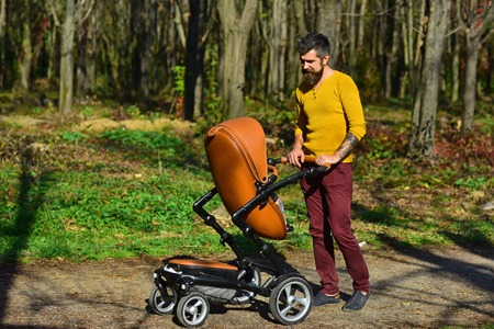 Father with pram on walk. Father push baby stroller in autumn park. This is what an awesome dad looks like