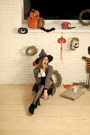 Halloween girl sitting on wooden floor.