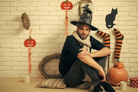 Halloween man sitting with gift box and cups on floor. Stock Photo