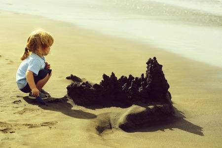 Cute baby boy builds sandcastle on sea beach Stock Photo - 109169814