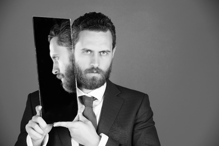 businessman, bearded serious man reflecting in mirror Stock Photo