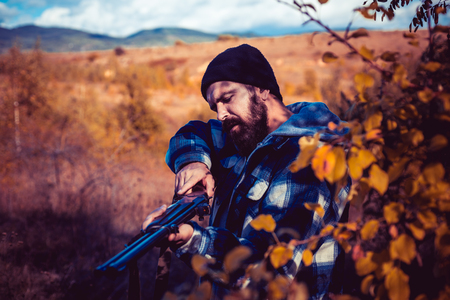Hunter with shotgun gun on hunt. Autumn hunting season. Closed and open hunting season. Poacher in the Forest. Mountain hunting.