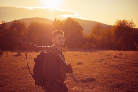 Rifle Hunter Silhouetted in Beautiful Sunset. Autumn hunting season. Autunm hunting.