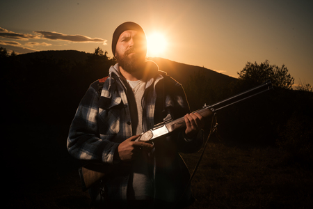American hunting rifles. Hunting without borders. Rifle Hunter Silhouetted in Beautiful Sunset.