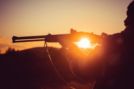 Trigger of the shotgun. Rifle Hunter Silhouetted in Beautiful Sunset. Silhouette of the hunter. Stock Photo