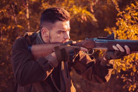 Hunter with shotgun gun on hunt. Autumn hunting season. Autunm hunting. Hunting without borders. Gun rifle.