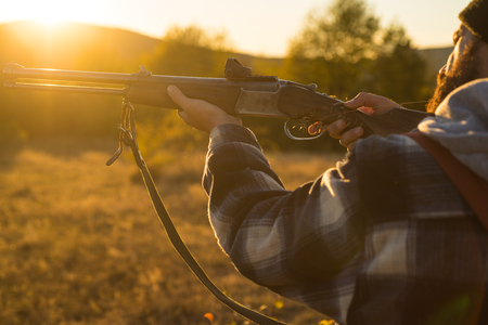 Rifle Hunter Silhouetted in Beautiful Sunset. Autumn hunting season. Track down.