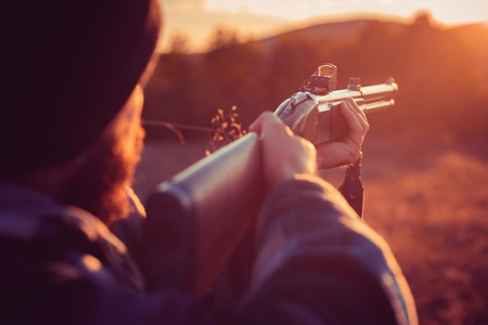 Close up snipers carbine at the outdoor hunting. Rifle Hunter Silhouetted in Beautiful Sunset. Autumn hunting season. Track down.