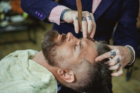 Ideas about Barbershop and Barber salon. Making haircut look perfect in barber shop. Fine Cuts. Professional hairstylist in barbershop interior. Hair Preparation is just for the dashing chap. Banco de Imagens